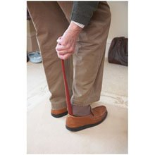 elderly man using a long shoe horn to put shoes on