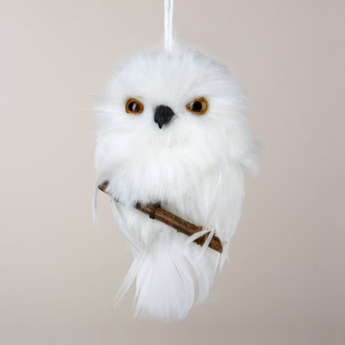 White snowy owl perched on branch ornament