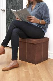 Woman sitting on the FHE Group microsuede storage ottoman