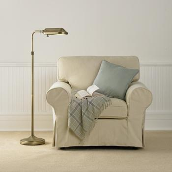 Heritage Natural Spectrum Floor Lamp illuminating a comfortable chair with a book on it.