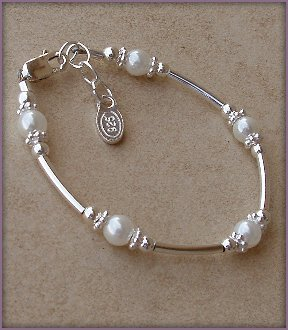 Madelyn Sterling Silver Childrens Girls Bracelet Jewelry This unique sterling silver bracelet is made with silver curved tubes and beautiful white Czech pearls accented by sparkling silver daisies on either side - a dainty and delicate touch! Size Medium 1-5 Years