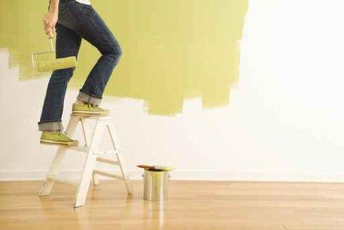 Legs of Woman Climbing Stepladder Holding Paint Roller. - 52