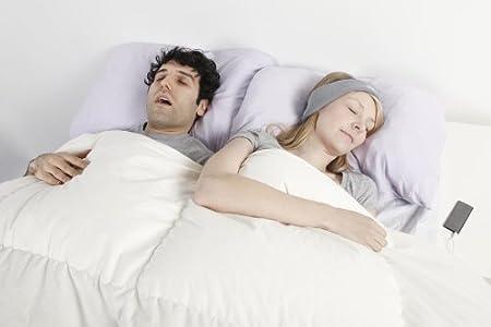woman with SleepPhones sleeping peacefully beside snoring man