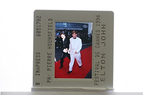 Slides photo of English pianist and singer Elton John walking on red carpet at the Cannes Festival and smiling. (Singers On Songwriting compare prices)