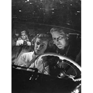Young Couple Snuggling in Convertible as They Intently Watch Movie at Drive-in Movie Theater Photographic Poster Print by J. R. Eyerman, 24x32