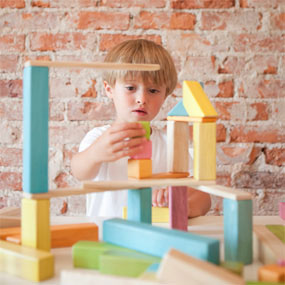 child building with Tegu Magnetic Wooden Blocks