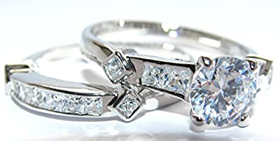 Free Engraving Of Your Choice! 2.45ct Simulated Diamond Ring And Band Set. Brilliant Round Center Stone. Princess Cut Side Setting Ring and Matching Band. Rhodium Electroplated. Remarkable Quality.