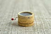 Caja de música manual redonda pentagrama antiguo con melodías de música clásico.