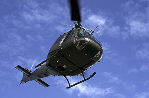 Former US Air Force Bell UH-1E Huey helicopter in flight by Daniel Karlsson/Stocktrek Images Art Print