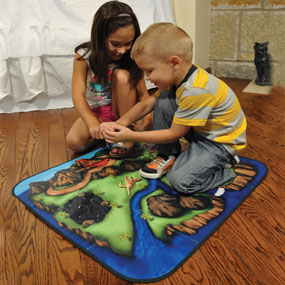 Children playing on dinosaur mat.