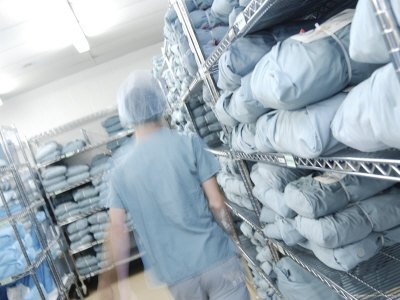 Doctor Walking Through Hospital Closet with Blue Sheets and Scrubs