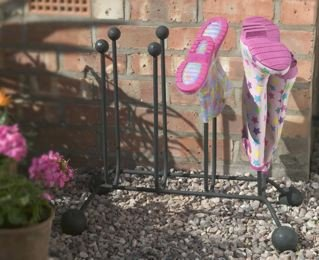 Handmade Wellington boot stand with Wellington Boots outside house in garden against wall resting on pebbles
