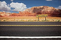 Desert blacktop road in Northern Arizona going through desert mountain landscape with a yellow road sign that says Welcome to Navajo Nation.
