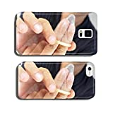young man unrolling a condom in his fingers cell phone cover case Samsung S5