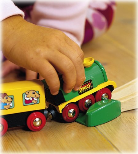 Brio wooden train set showing hand of child holding train