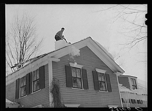 Shoveling heavy snow off roof of house in Woodstock,Vermont