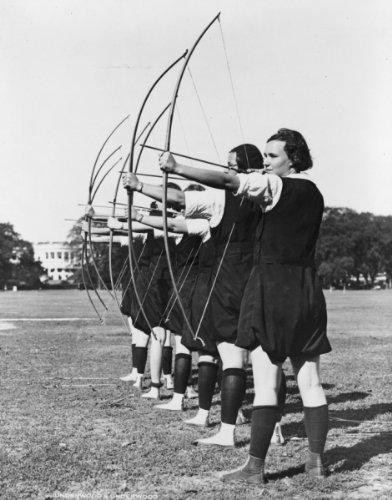 1931 photo Female students of George Washington University practicing archery with the White House i