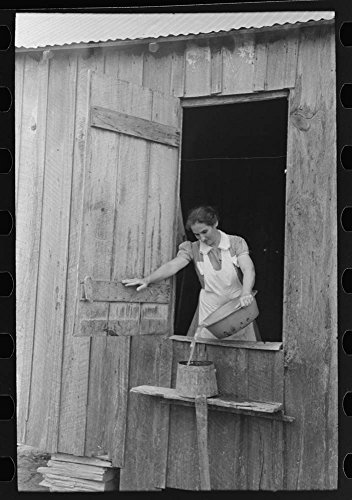 Day laborer with sugarcane knife in front of his shack home near New Iberia, Louisiana