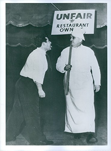 Vintage photo of Man showing tongue to man, holding a placard.