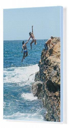 canvas-print-of-two-girls-diving-off-cliff-into-surf