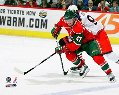 marc-andre-bergeron-47-of-the-minnesota-wild-skates-with-the-puck-while-being-defended-by-jakub-vora