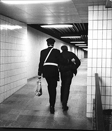 vintage-photo-of-a-police-officer-escorts-a-man-out-of-a-subway