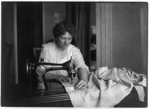 Photo Woman sewing with a Singer sewing machine 1917