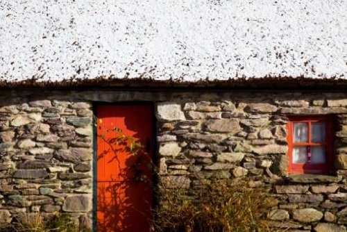 A Stone House with an Orange Door and Window Frame and Snow on the Roof - 42