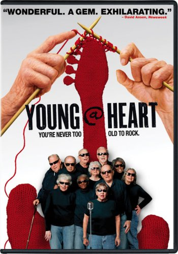 group of older adults wearing black sunglasses in front of red guitar being knitted by two hands