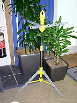 multi hanger clothes stand next to pot plants and fire extinguisher