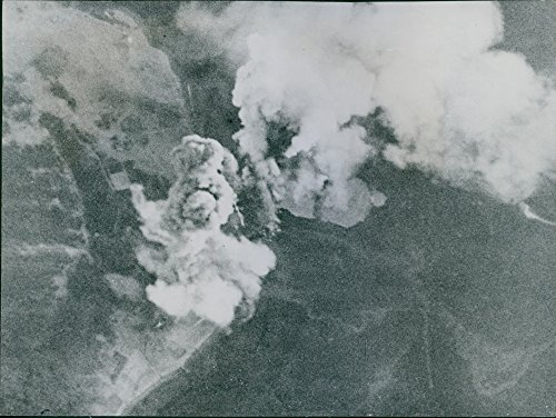 Dramatic end of the Tirpitz: capsizes after attack by bomber.Smoke from the bombs towers over the target completely obscured.