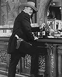 The Shootist John Wayne iconic pose at saloon bar whisky bottle gun belt 8x10 Promotional Photo