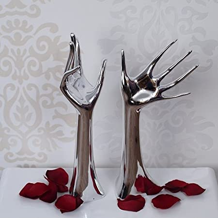 Two silver mannequin jewellery stands on a white plinth with red rose petals for decoration