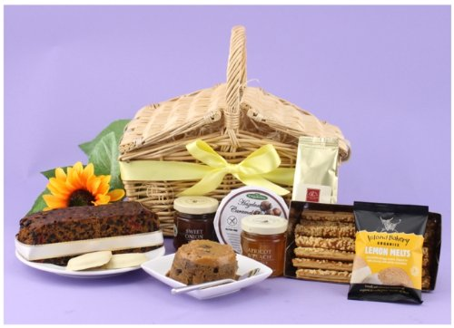 HAMPER TREAT - Twin flap traditional handwoven willow hamper packed with treats including fruit cake, Scottish oat pudding with delicious topping, lemon melt biscuits, sweet onion relish, apricot and peach preserve, cheese straws and after dinner coffee. Food hampers from Web Hampers.