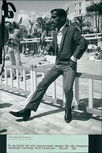 Original Vintage Photo Of Sammy Davis Jr. Sitting On Barricade While Holding Microphone.