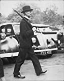 Vintage photo of Arthur Neville Chamberlain stepping out in military style, returns to no.10 downing street after his daily walk.