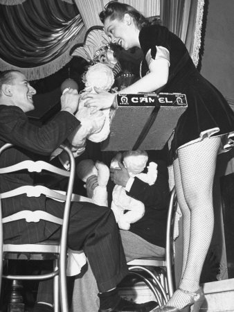 Cigarette Girl Playing with a Stuffed Animal with a Patron at the Opening of the Diamond Horseshoe Photographic Poster Print by John Phillips, 12x16