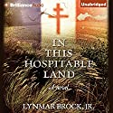 In This Hospitable Land Audiobook by Lynmar Brock Narrated by David Baker