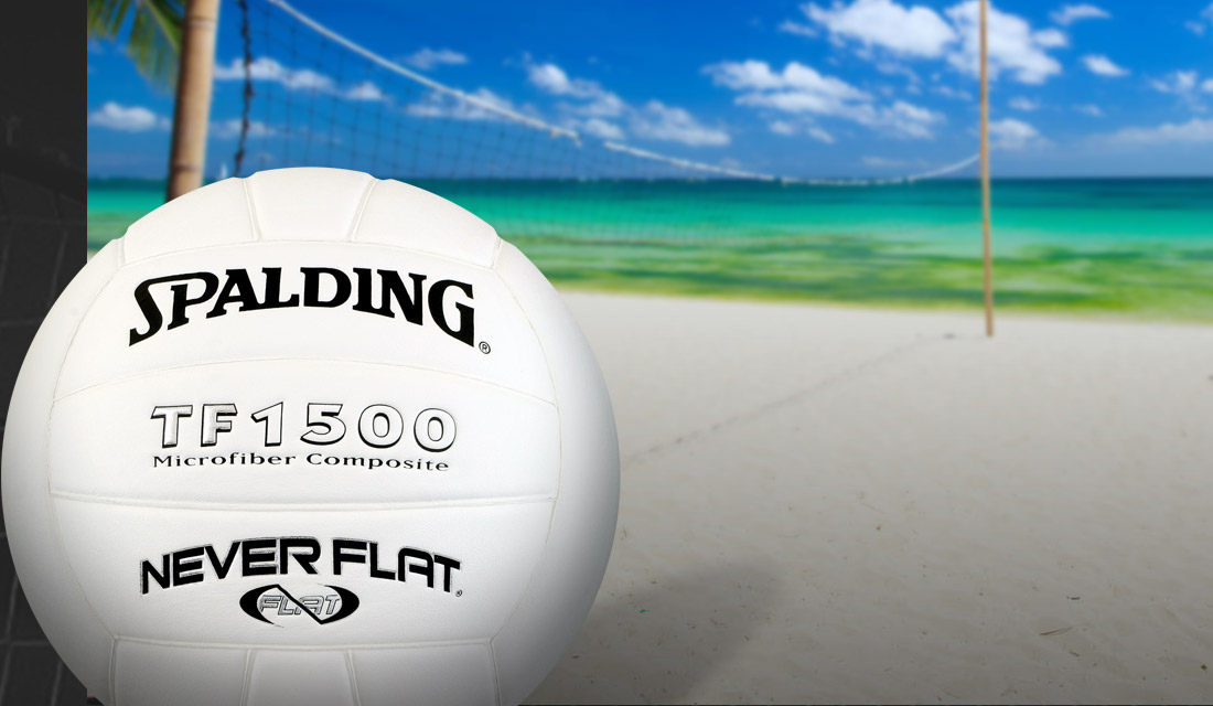 Spalding Neverflat Volleyball outdoors on beach with the ocean and a net in the background