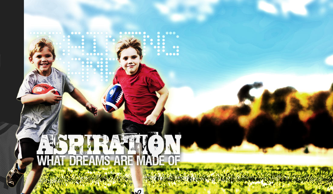 Two Young Boys Running in Field Holding their Spalding Rookie Gear Footballs